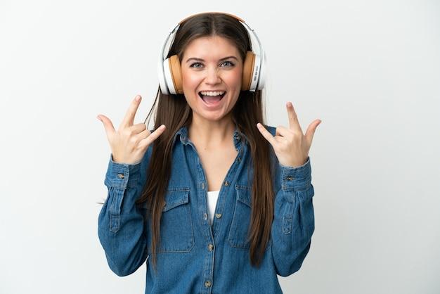 ロックジェスチャーを作る音楽を聴いて白い背景で隔離の若い白人女性