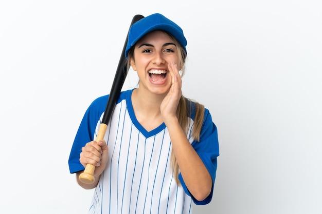 Молодая кавказская женщина, изолированная на белом фоне, играет в бейсбол и кричит с широко открытым ртом
