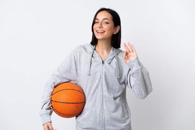 バスケットボールをしてokサインを作る白い背景で隔離の若い白人女性