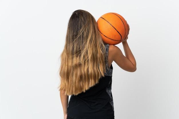 後ろの位置でバスケットボールをしている白い背景で隔離の若い白人女性