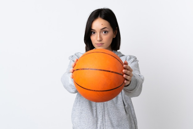 バスケットボールをしている白い背景で隔離の若い白人女性