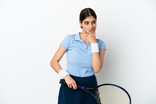 テニスをして考えている白い背景で隔離の若い白人女性