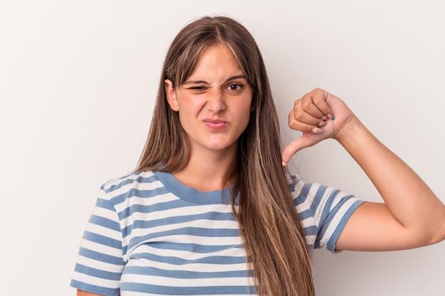親指を下に、失望の概念を示す白い背景で隔離の若い白人女性。