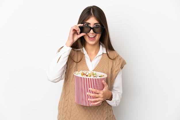 3dメガネに驚いて、ポップコーンの大きなバケツを保持している白い背景で隔離の若い白人女性