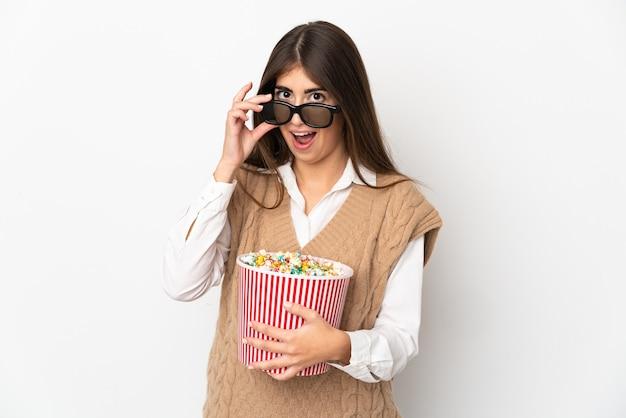흰색 배경에 격리된 젊은 백인 여성은 3d 안경에 놀라고 큰 팝콘 양동이를 들고 있다