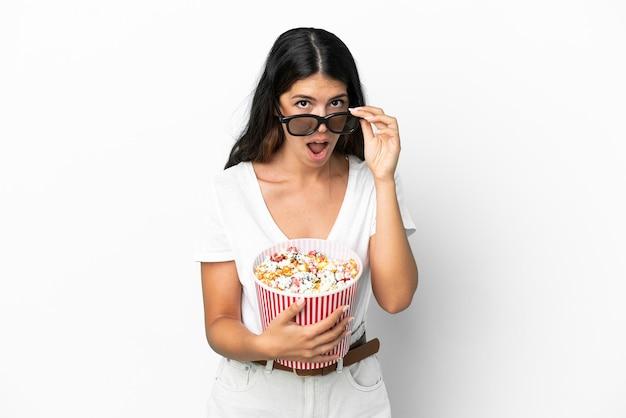 Молодая кавказская женщина, изолированная на белом фоне, удивлена в 3d-очках и держит большое ведро попкорна