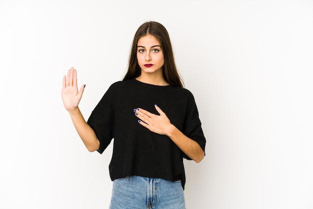 胸に手を置いて、誓いを立てて白い背景で隔離の若い白人女性。