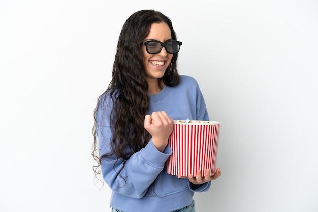 3dメガネで白い背景に分離され、側面を見ながらポップコーンの大きなバケツを保持している若い白人女性
