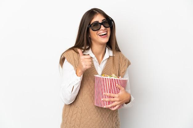 3dメガネで白い背景に分離され、正面を指してポップコーンの大きなバケツを保持している若い白人女性