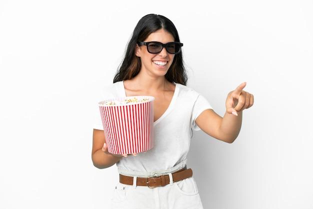 Молодая кавказская женщина изолирована на белом фоне с 3d-очками и держит большое ведро попкорна, указывая вперед