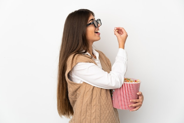 3dメガネとポップコーンの大きなバケツを保持している白い背景で隔離の若い白人女性