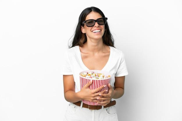 흰색 배경에 3d 안경을 쓰고 큰 팝콘 양동이를 들고 있는 백인 젊은 여성