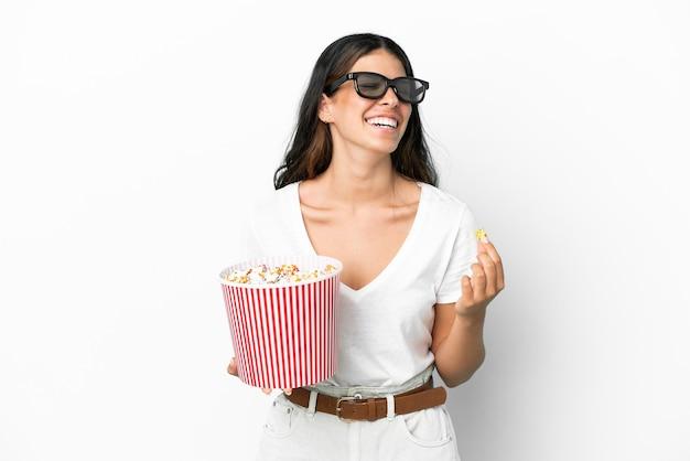 Молодая кавказская женщина изолирована на белом фоне с 3d-очками и держит большое ведро попкорна