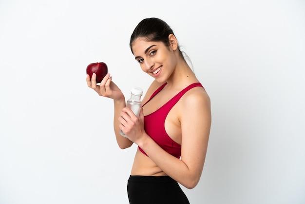 Молодая кавказская женщина изолирована на белом фоне с яблоком и бутылкой воды