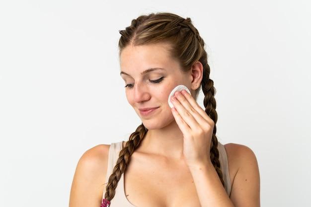 彼女の顔から化粧を削除するための綿のパッドと白い背景で隔離の若い白人女性