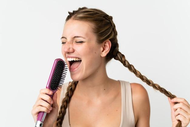 髪の櫛と歌と白い背景で隔離の若い白人女性