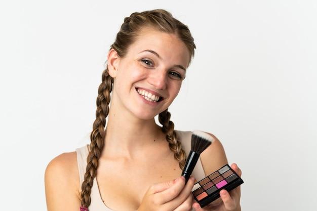 Молодая кавказская женщина изолирована на белом фоне с палитрой макияжа и счастлива