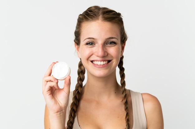 Молодая кавказская женщина изолирована на белом фоне с увлажняющим кремом и счастьем
