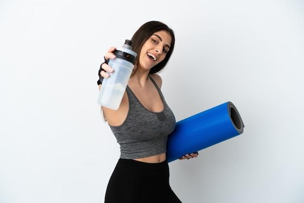 Молодая кавказская женщина изолирована на белом фоне со спортивной бутылкой с водой и с циновкой