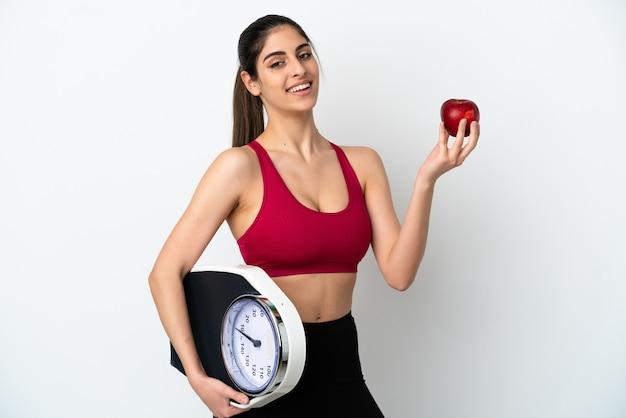 Молодая кавказская женщина изолирована на белом фоне с весами и яблоком
