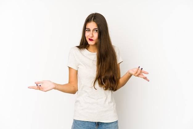Молодая кавказская женщина, изолированные на белом, сомневаясь и пожимая плечами в вопросительном жесте.