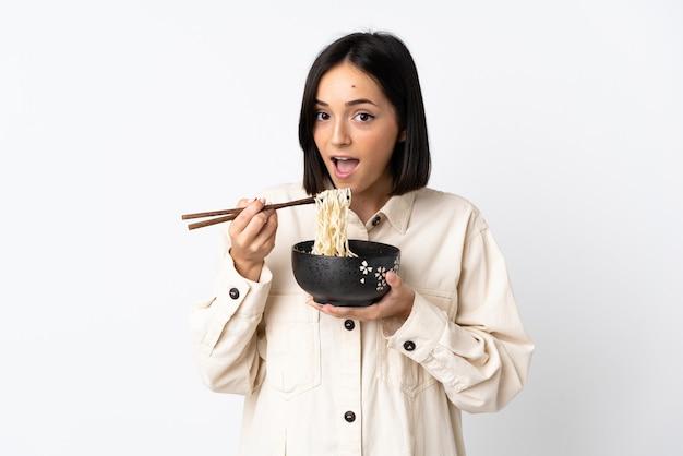 箸で麺のボウルを保持し、それを食べる白で隔離の若い白人女性