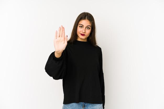 Молодая кавказская женщина, изолированные на белом, стоя с протянутой рукой, показывая знак остановки, предотвращая вас.