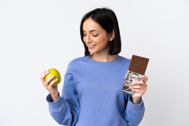 片方の手にチョコレートタブレット、もう片方の手にリンゴを取る白で隔離の若い白人女性