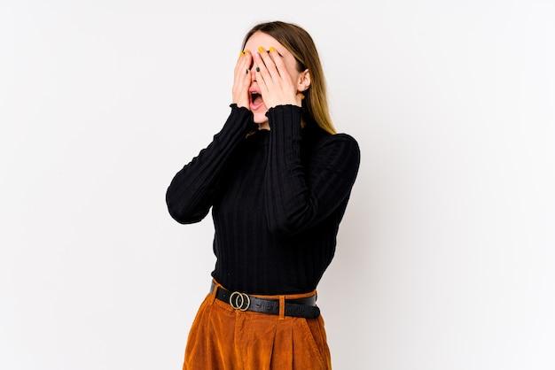 手で目を覆っているのを恐れて白い壁に分離された若い白人女性。
