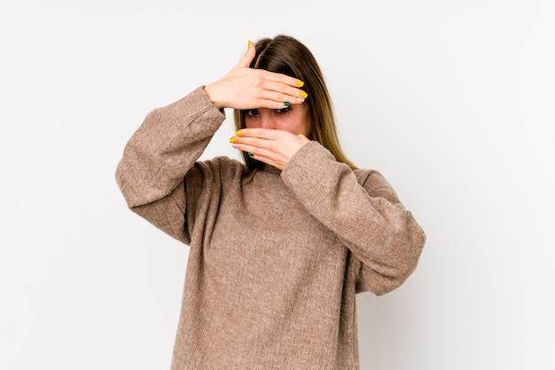 白い壁に分離された若い白人女性は、恥ずかしそうに顔を覆っている指を通して点滅します。
