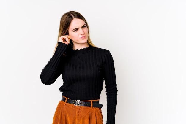 若い白人女性が指で耳を覆う白い壁に分離され、ストレスがたまり、大声で絶望的です。