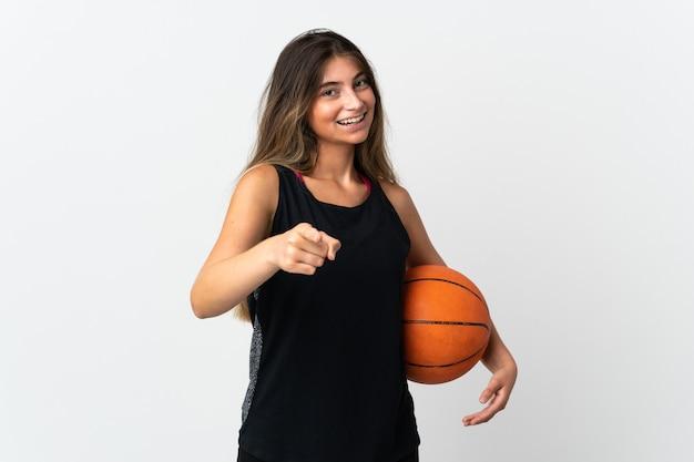 バスケットボールをし、正面を指して白い壁に孤立した若い白人女性