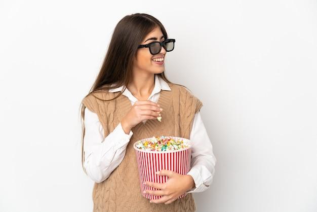 3dメガネで白い壁に隔離され、ポップコーンの大きなバケツを保持している若い白人女性