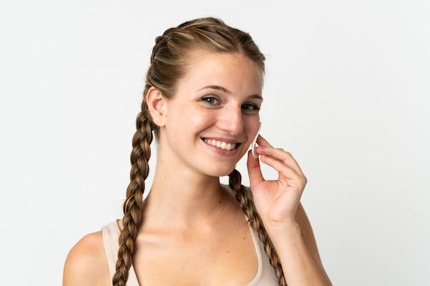 그녀의 얼굴에서 메이크업을 제거하기위한 목화 패드와 함께 흰색에 고립 된 젊은 백인 여자