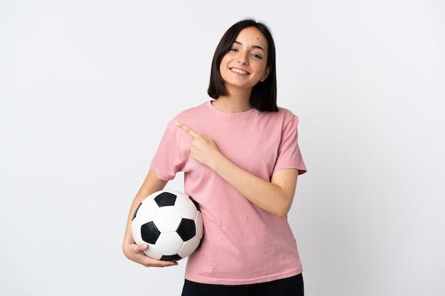 축구 공 흰색 절연 및 측면을 가리키는 젊은 백인 여자
