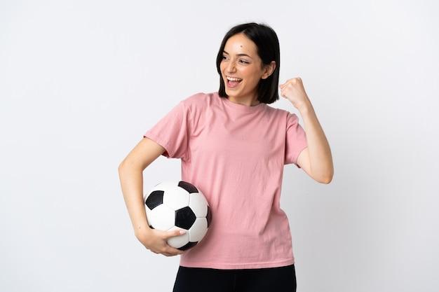 Молодая кавказская женщина, изолированная на белом с футбольным мячом, празднует победу