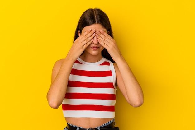 손으로 눈을 덮고 두려워 노란색 배경에 고립 된 젊은 백인 여자.