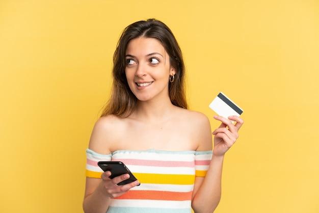 생각하는 동안 신용 카드로 모바일로 구매하는 노란색 배경에 고립 된 젊은 백인 여자