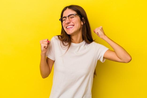 勝利、情熱と熱意、幸せな表現を祝う黄色の背景に孤立した若い白人女性。