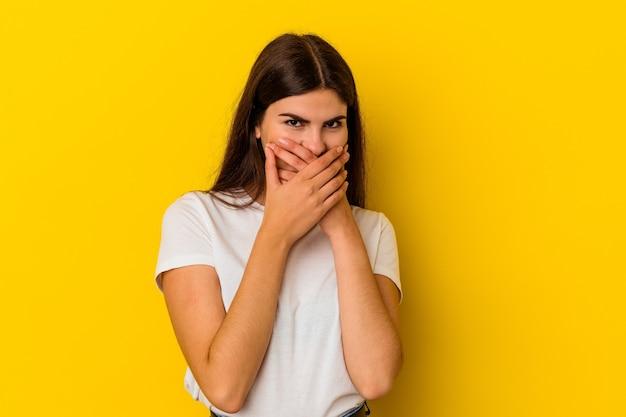 걱정 찾고 손으로 입을 덮고 노란색 배경에 고립 된 젊은 백인 여자.