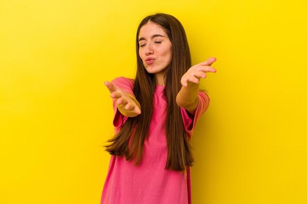 黄色の背景に孤立した若い白人女性は、唇を折り、手のひらを持って空気のキスを送信します。