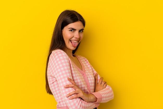 舌を突き出して面白いとフレンドリーな黄色の背景に分離された若い白人女性。