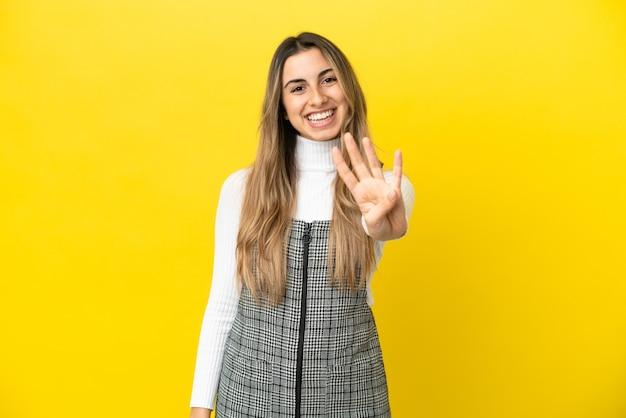 Молодая кавказская женщина изолирована на желтом фоне счастлива и считает четыре пальцами