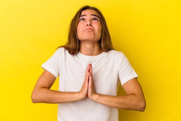 口の近くで祈って手をつないで黄色の背景に分離された若い白人女性は、自信を持っています。