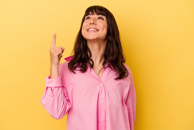 노란색 배경에 고립 된 젊은 백인 여자는 빈 공간을 보여주는 두 앞 손가락으로 나타냅니다.
