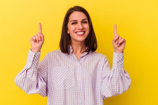 Молодая кавказская женщина, изолированная на желтом фоне, показывает обоими указательными пальцами вверх, показывая пустое пространство.