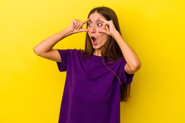 노란색 배경에 격리된 젊은 백인 여성은 성공의 기회를 찾기 위해 눈을 떴습니다.