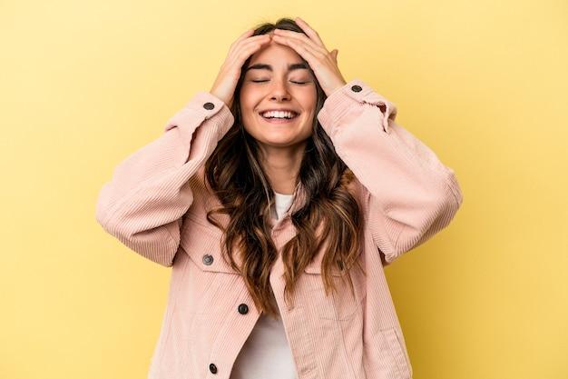 노란색 배경에 격리된 젊은 백인 여성은 머리에 손을 얹고 즐겁게 웃고 있습니다. 행복 개념입니다.