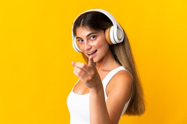 音楽を聞いて黄色の背景に分離された若い白人女性