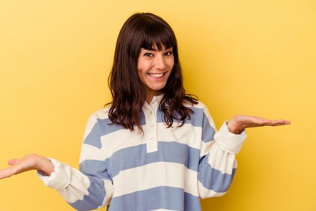 노란색 배경에 고립 된 젊은 백인 여자는 팔으로 규모를 만들고, 행복하고 자신감을 느낍니다.